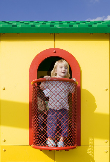 play house. child on balcony of yellow building in amusement park